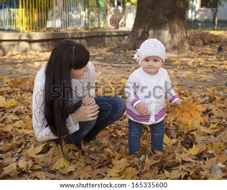 pretty little baby girl  in the autumn park having fun with her mother - stock photo