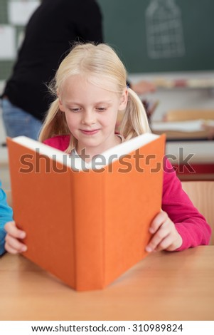 Pretty little blond girl sitting at a desk reading a large hardcover textbook in class at school - stock photo