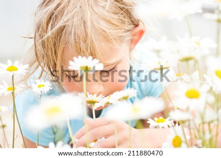 Pretty Little Blond Girl Smelling Daisies on the Beach - stock photo