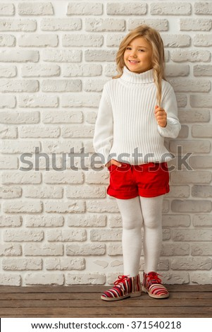 Pretty little blonde girl looking in camera and smiling while standing against white brick wall - stock photo