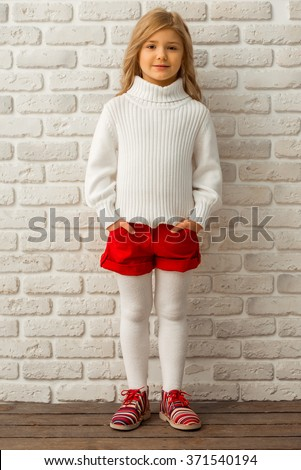 Pretty little blonde girl looking in camera while standing against white brick wall - stock photo