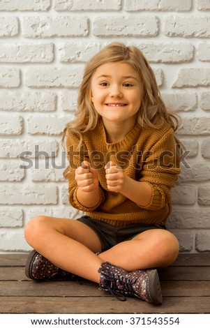 Pretty little blonde girl showing emotions while sitting cross-legged against white brick wall - stock photo