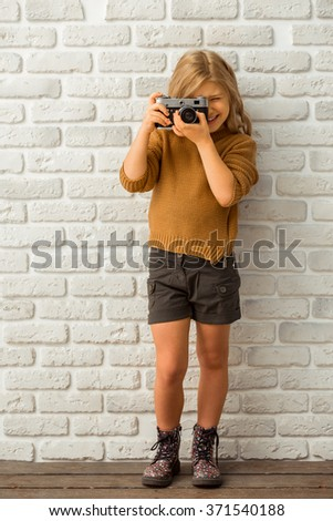 Pretty little blonde girl smiling and making a photo while standing against white brick wall - stock photo