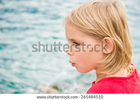 Pretty Little Blonde Girl Whistling by the Lake - stock photo