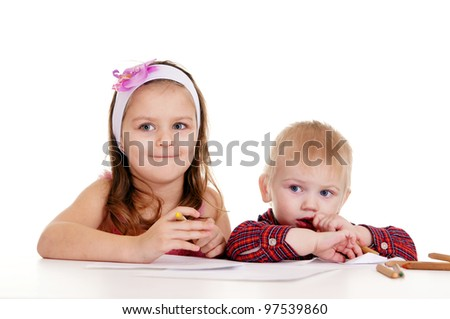 pretty little  boy and girl drawing at table