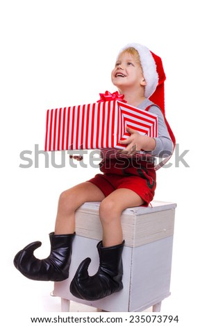 Pretty little boy with Santa Claus helper costume holding big striped gift box and looking up. Studio portrait isolated over white background - stock photo
