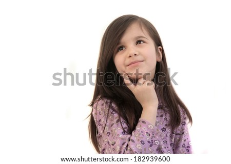 Pretty little brunette 6 year old girl thinking, looking up with finger to face on a white background and copyspace - stock photo