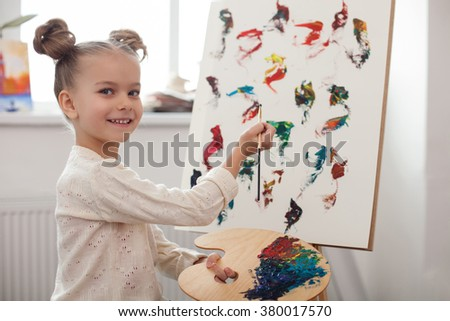 Pretty little child is painting with joy - stock photo