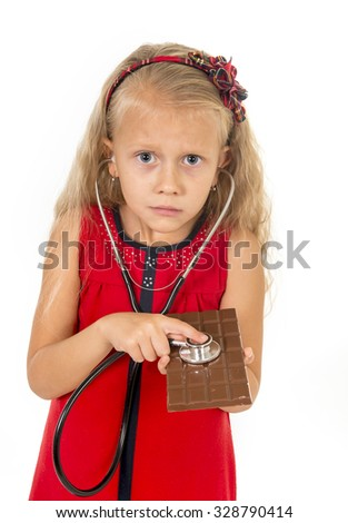 pretty little female child in red dress with stethoscope on chocolate bar looking worried in unhealthy nutrition habit ,  sugar sweet abuse and excess and healthy diet concept isolated on white