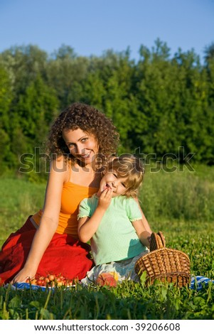 pretty Little Girl and Young Women eats sweet cherries on picnic