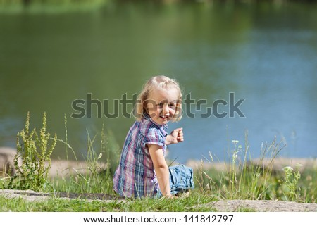 Pretty little girl at the lake sitting on a rock overlooking the water looking back over her shoulder at the camera with a lovely smile