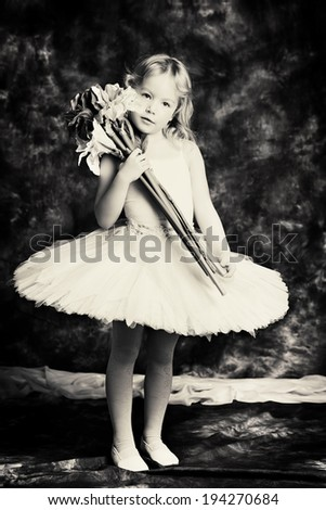 Pretty little girl ballerina in tutu posing over vintage background. Black-and-white photo.