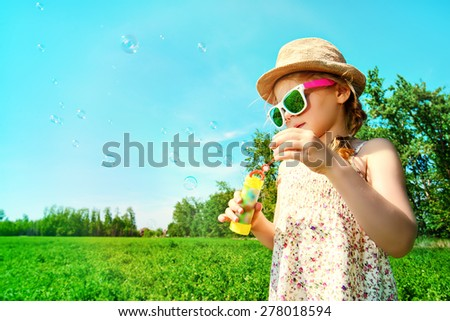 Pretty little girl blows bubbles on a meadow in summer day. Happy childhood. Blue sky. - stock photo