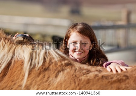 Pretty little girl brushing her horse and looking over the top of its back with a lovely smile - stock photo