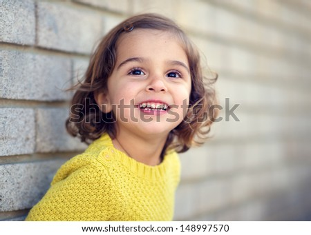Pretty Little Girl by Brick Wall - stock photo