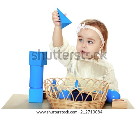 pretty little girl collects the dice sitting at the table.The concept of development of the child younger years. - stock photo