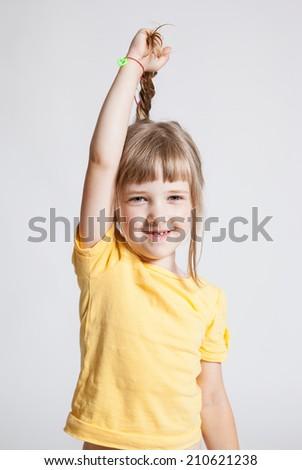 Pretty little girl demonstrating her beautiful long hair, white background - stock photo