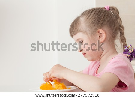 Pretty little girl don't want to eat an orange - stock photo