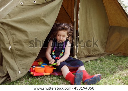 Pretty little girl dressed in a black dress denim jacket and red boots played near the tent in yard