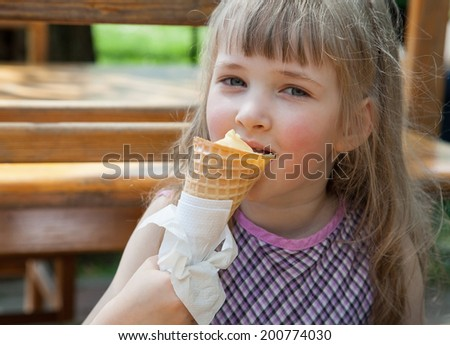 Pretty little girl eating an ice-cream in a summer cafe