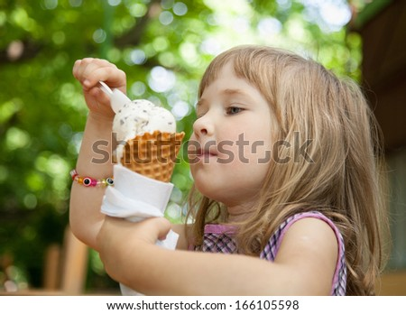 Pretty little girl eating an ice cream outdoors - stock photo