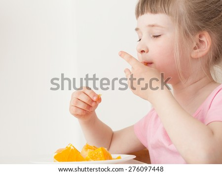 Pretty little girl eating an orange with enjoyment - stock photo