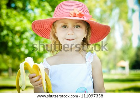 Pretty little girl eating banana - stock photo