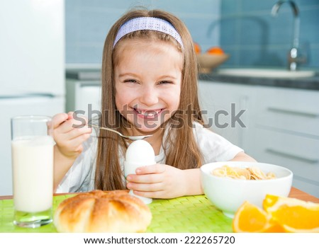 pretty little girl eating egg in the kitchen - stock photo