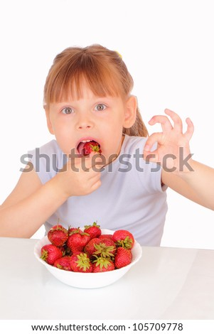 Pretty little girl eating strawberries