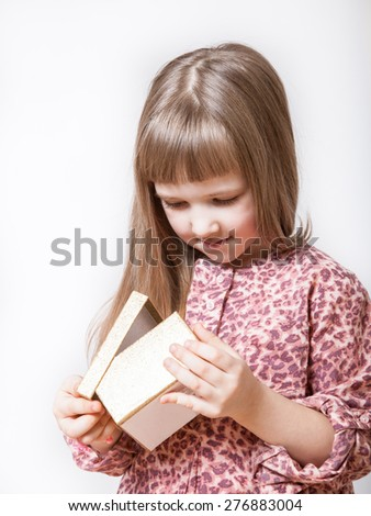 Pretty little girl examining a gift box - stock photo