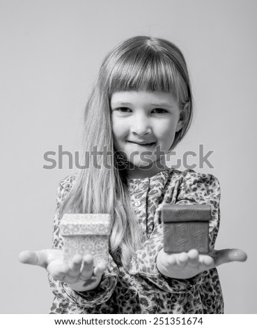 Pretty little girl holding a gift boxes on neutral background - stock photo