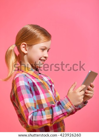 Pretty little girl holding a tablet on pink background in profile.