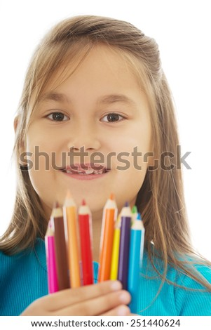Pretty little girl holding crayons in hands - stock photo
