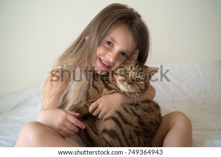 Pretty little girl holding her cat
