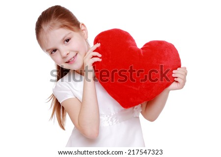 Pretty little girl holding red valentine's heart