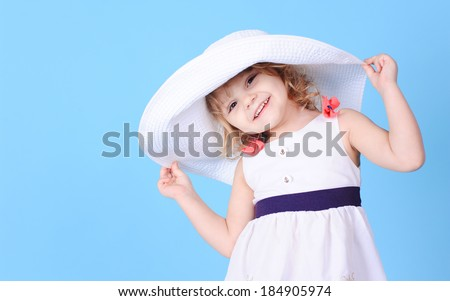 Pretty little girl holding summer hat on blue