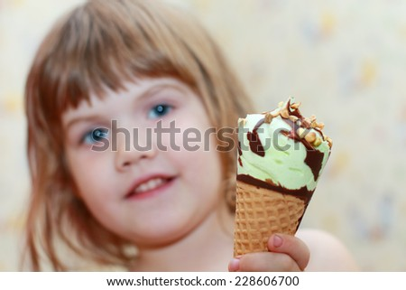Pretty little girl holds ice cream. Shallow dof. Focus on ice cream - stock photo