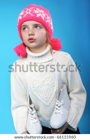 pretty little girl in a winter cap and with the skates