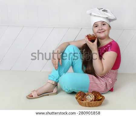 Pretty little girl in chief hat sits on floor and going to eat buns - stock photo