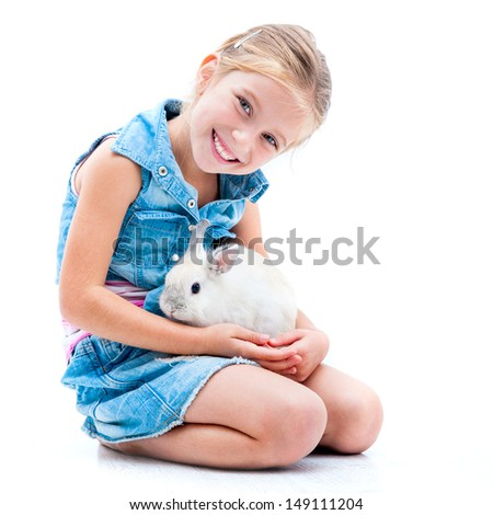 pretty little girl in denim clothing playing with white rabbit - stock photo
