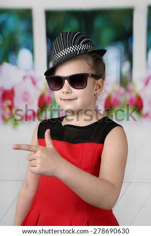 Pretty little girl in hat and sunglasses shows index finger - children beauty and fashion concept - stock photo
