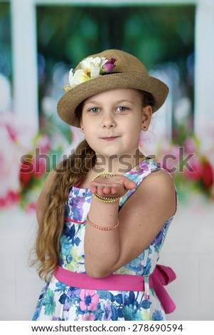 Pretty little girl in hat blows kiss - children beauty and fashion concept - stock photo
