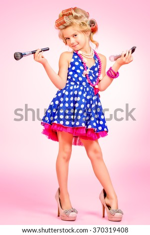 Pretty little girl in her mother's shoes and hair curlers. Kid's fashion, cosmetics. Pin-up style. - stock photo