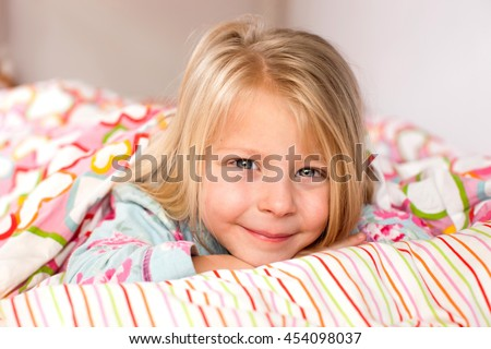 Pretty little girl in pajamas lying in bed in the morning