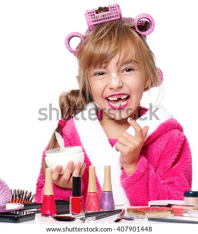 Pretty little girl in pink bathrobe with curlers on her head applying cream on white background