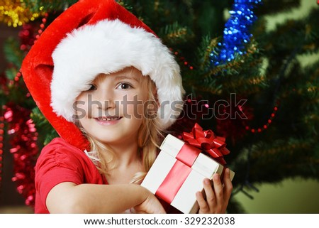 Pretty little girl  in santa cap near Cristmas tree  - stock photo