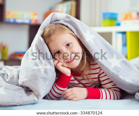 Pretty little girl in sleepwear lying under blanket