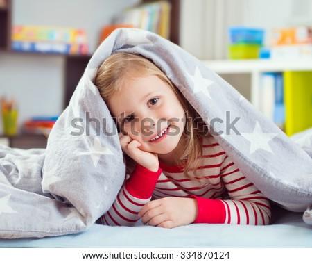 Pretty little girl in sleepwear lying under blanket - stock photo