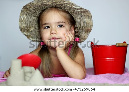 Pretty little girl in swimming clothes with toy shovel and pain in sand over white background, summer vacation concept