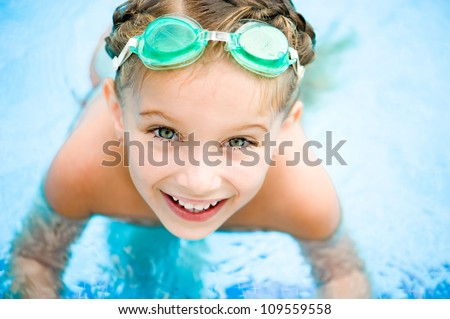 Pretty little girl in swimming pool - stock photo
